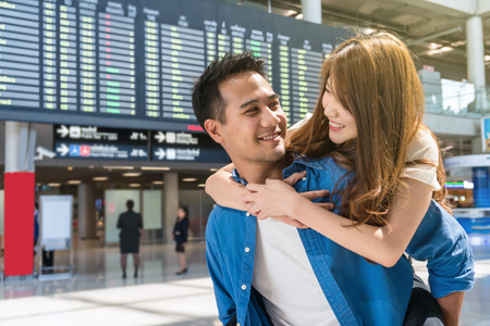 Happiness Asian couple traveler at the flight information screen in modern an airport, lifestyle travel and transportation concept. Stock Photo