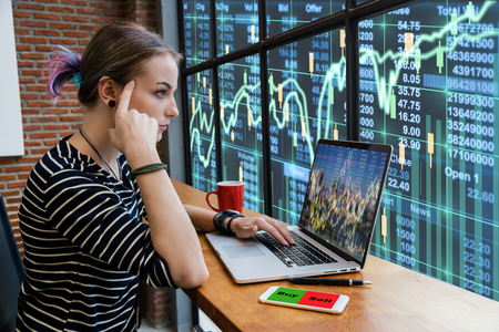 Hipster young Woman freelancer thinking about her job and using computer laptop showing trading graph with the stock exchange trading graph screen background, Business financial and forex concept