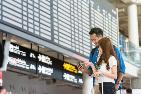 Asian couple traveler using the smart mobile phone for check-in at the flight information screen in modern an airport, travel and transportation with technology concept.