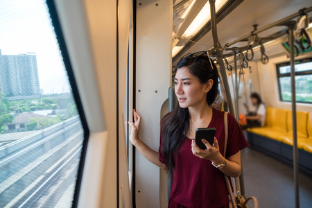 Asian woman passenger with casual suit using smart mobile phone in the BTS Skytrain rails or MRT subway for travel in the big city, lifestyle and transportation concept