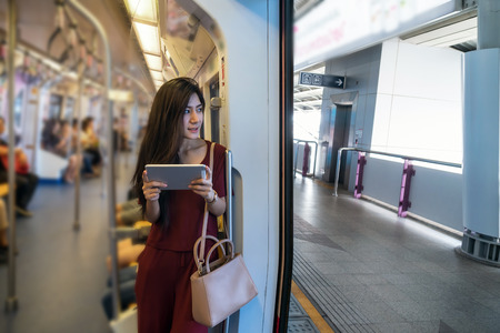 Asian woman passenger with casual suit using the technology tablet in the BTS Skytrain rails or MRT subway for travel in the big city, lifestyle and transportation concept