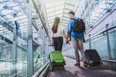 Asian couple traveler with suitcases at the airport. Lover travel and transportation with technology concept. Stock Photo