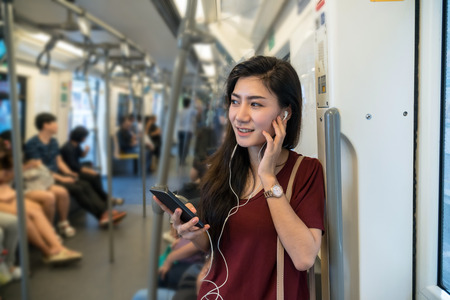 Asian woman passenger with casual suit using and listening the song via smart mobile phone in the BTS Skytrain rails or MRT subway for travel in the big city, lifestyle and transportation concept