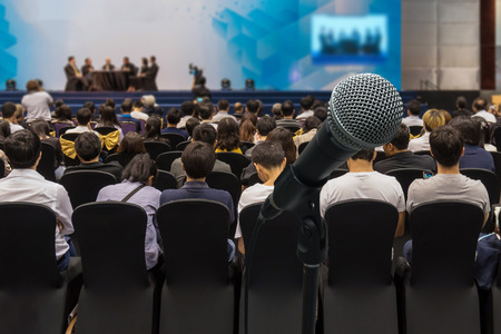 attendee: Microphone with Abstract blurred photo of conference hall or meeting room with attendee background, business and education concept Stock Photo