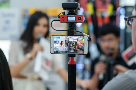 BANGKOK, THAILAND - SEP 13, 2017 : Closeup smart mobile phone taking Live over photo blurred of presenters with guest introduce the product background on September 13, 2017 at Bangkok, Thailand.