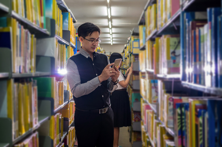 working on school project: Portrait of Asian teacher standing using smart mobile phone and choosing the book for giving lesson in libraly room, University education concept