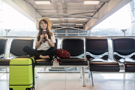Happy Asian woman traveler holding the passport with suitcases in modern an airport, travel and transportation with technology concept.