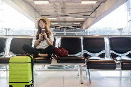 Voyageur de femme asiatique heureuse détenteurs du passeport avec valises dans un aéroport moderne, transport et transport avec concept technologique. Banque d'images - 89550559