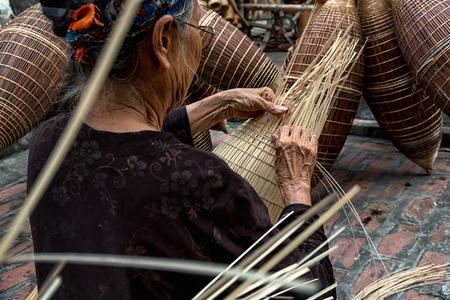 Alte vietnamesische weibliche Handwerkerhände der Nahaufnahme, welche die traditionelle Bambusfischfalle oder -webart am alten traditionellen Haus in Thu-sy-Handelsdorf, Hung Yen, Vietnam, traditionelles Künstlerkonzept machen Standard-Bild - 89568767