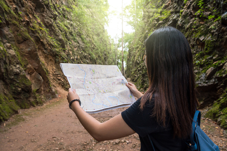 Back side of young traveler see the map in the deep forest, Hellfire Pass at kanchanaburi, Thailand, Travel and transportation concept