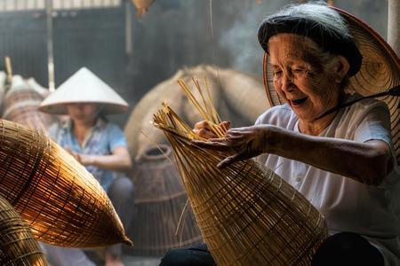 Alter vietnamesischer weiblicher Handwerker, der die traditionelle Bambusfischfalle oder -webe am alten traditionellen Haus in Thu-sy-Handelsdorf, Hung Yen, Vietnam, traditionelles Künstlerkonzept macht Standard-Bild - 89568769