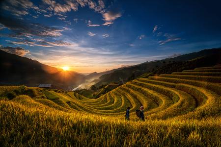 2人の未定義のベトナムのモン族が、北西ベトナムの日の出の収穫準備のために水田台地の幻想的な風景の中を歩いている。Mu 蒼チャイ, 円バイ州, ベ