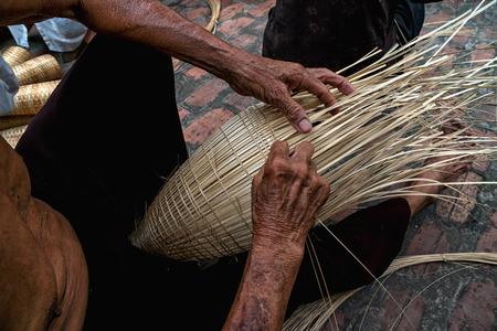 Alte vietnamesische männliche Handwerkerhände der Nahaufnahme, welche die traditionelle Bambusfischfalle oder -webe am alten traditionellen Haus in Thu-sy-Handelsdorf, Hung Yen, Vietnam, traditionelles Künstlerkonzept machen Standard-Bild - 89550953