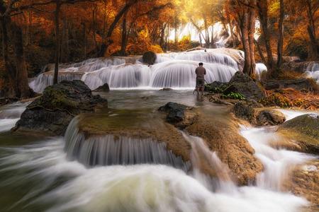 Photographer taking photo scene of Beautiful waterfall in the deep forest,Pha Tat Waterfall, Kanchanaburi province, thailand, Nature travel concept Imagens