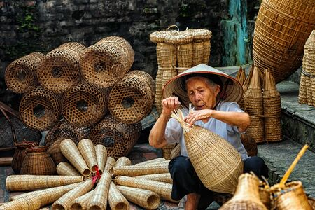 Old Vietnamese female craftsman making the traditional bamboo fish trap or weave at the old traditional house in Thu sy trade village, Hung Yen, Vietnam, traditional artist concept Standard-Bild - 95066089
