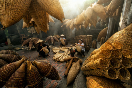 Group of Old Vietnamese female craftsman making the traditional bamboo fish trap or weave at the old traditional house in Thu sy trade village, Hung Yen, Vietnam, traditional artist concept Standard-Bild - 90727952