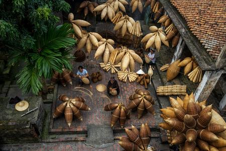Draufsicht der Gruppe des alten vietnamesischen weiblichen Handwerkers, der die traditionelle Bambusfischfalle oder -webart am alten traditionellen Haus in Thu-sy-Handelsdorf, Hung Yen, Vietnam, traditionelles Künstlerkonzept macht Standard-Bild - 90668456