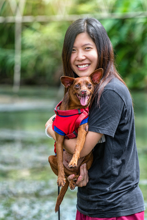 The asian women mini dog in brown color over the lake at the resort in deep forest, Lover and animal with nature concept