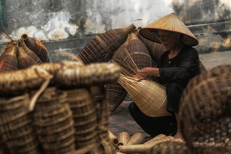 Closeup Old Vietnamese female craftsman making the traditional bamboo fish trap or weave at the old traditional house in Thu sy trade village, Hung Yen, Vietnam, traditional artist concept Standard-Bild