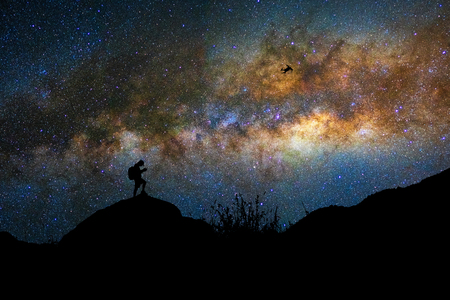 Silhouette of photographer with drone over the milky way on the dark sky background, photographer and transportation with astrophotography concept