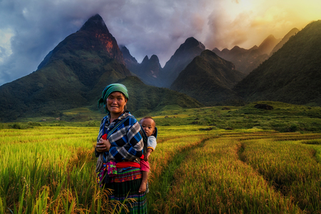 YENBAI - SEP 22 : Undefined Vietnamese Hmong with her baby standing in the rice fied on september 22, 2017 at cha vu near sapa,Yenbai province, northwest of Vietnam.
