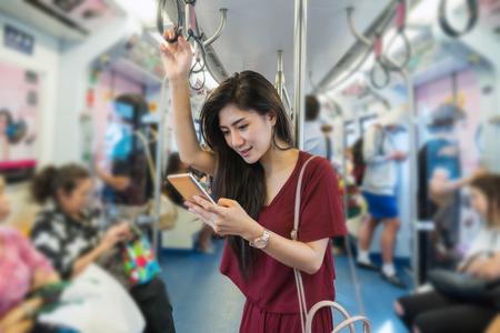 Aziatische vrouwenpassagier met toevallig kostuum die de slimme mobiele telefoon in de BTS Skytrain-sporen of MRT-metro gebruiken voor reis in het grote stad, levensstijl en vervoersconcept Stockfoto