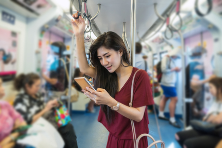 Asian woman passenger with casual suit using the smart mobile phone in the BTS Skytrain rails or MRT subway for travel in the big city, lifestyle and transportation concept