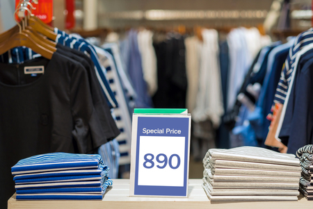 ショッピング、ビジネスファッション、広告コンセプトのショッピングデパートでシャツのスタック上の特別価格モックアップ広告表示フレーム設