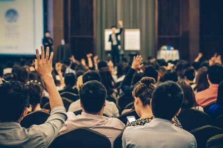 Alto-falante no palco com vista traseira do público na sala de conferências ou seminário reunião, negócios e educação conceito
