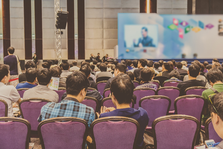 Speakers on the stage with Rear view of Audience in the conference hall or seminar meeting, business and education about investment concept Stock Photo