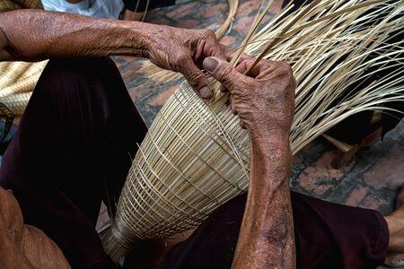 Alte vietnamesische männliche Handwerkerhände der Nahaufnahme, welche die traditionelle Bambusfischfalle oder -webe am alten traditionellen Haus in Thu-sy-Handelsdorf, Hung Yen, Vietnam, traditionelles Künstlerkonzept machen Standard-Bild - 91987593
