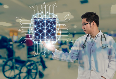 Asian Doctor with the stethoscope equipment hand holding the Artificial intelligence of brain technology over Abstract photo blurred of hospital background, AI and physician concept Foto de archivo