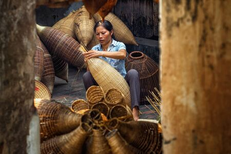 Old Vietnamese female craftsman making the traditional bamboo fish trap or weave at the old traditional house in Thu sy trade village, Hung Yen, Vietnam, traditional artist concept Standard-Bild - 95066865