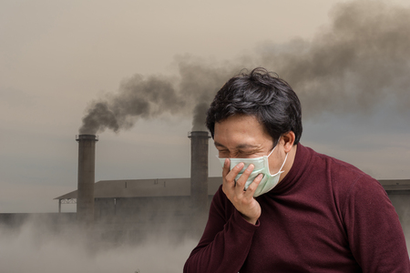 Asian man wearing the face mask against air pollution with coughing over the Smokestack Factory with black smoke on the sky with cloud, healthcare with industry and pollution concept Stock Photo