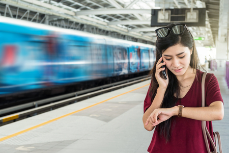 Asian woman passenger with casual suit watching the clock and calling the mobile phone in the BTS Skytrain rails or MRT subway for travel in the big city, lifestyle and transportation concept Foto de archivo