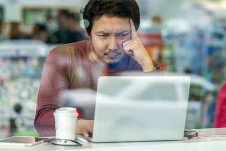Portrait of asian businessman in casual suit using technology laptop for working in serious and exhausted action at the desk beside the glass in modern office,Business and lifestyle concept