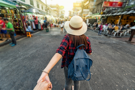Back side of Young Asian traveling women leading by holding her boyfriend hand in Khaosan Road walking street in evening at Bangkok, Thailand, traveleling together and tourist with follow me concept