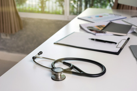 Stethoscope on the workplace table with some part of computer set and keyword with paper document office in the modern hospital or clinic, healthcare and physician concept