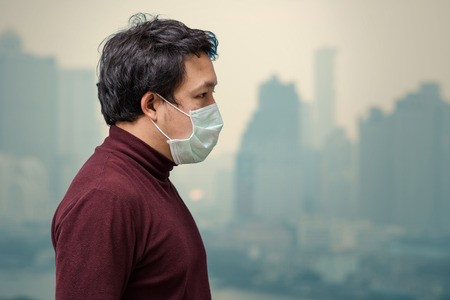 Aziatische mens die het gezichtsmasker tegen luchtvervuiling draagt op het balkon van Hoge Flat die verontreiniging en zware mist over de cityscape van Bangkok achtergrond, gezondheidszorgconcept kan zien
