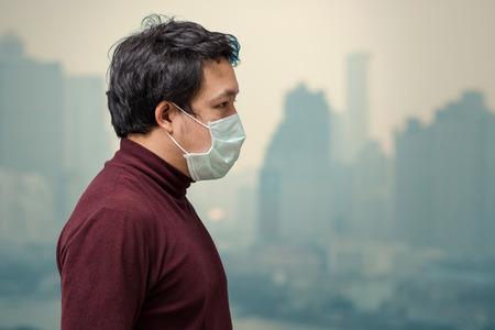 Hombre asiático con la mascarilla contra la contaminación del aire en el balcón del High Apartment, que puede ver la contaminación y la densa niebla sobre el fondo del paisaje urbano de Bangkok, el concepto de salud Foto de archivo