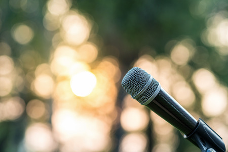 Microphone on the stage over the Abstract blurred photo of green tree with sunset light background, Musical and presentation concept Foto de archivo