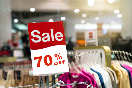 sale 70% mock up advertise display frame setting over the stack of shirt in the shopping department store for shopping, business fashion and advertisement concept Foto de archivo
