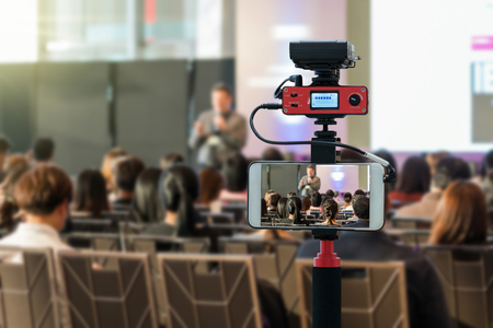 Closeup smart mobile phone taking Live over Speakers on the stage with Rear view of Audience in the conference hall or seminar meeting, technology live streaming and broadcast concept Standard-Bild
