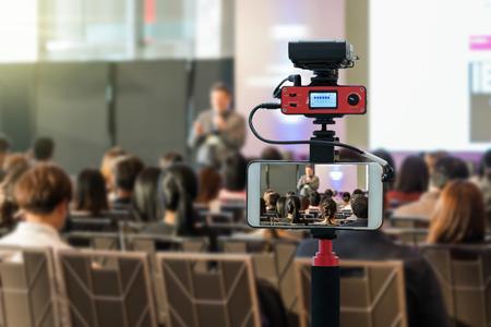Primo piano del telefono cellulare intelligente che prende in diretta gli altoparlanti sul palco con vista posteriore del pubblico nella sala conferenze o nella riunione del seminario, tecnologia live streaming e concetto di trasmissione