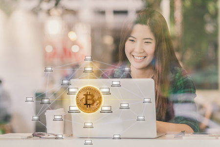Closeup Asian businesswoman hand using technology tablet with Bitcoins mockup and Distributed computer network hologram in workplace co-working space,blockchain and bitcoin concept