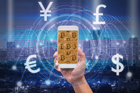 holding smart phone showing the financial technology with block chain over the innovation technology virtual screen on cityscape background, US dollar and other currency,business Fin tech concept