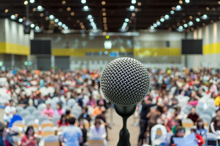 Microphone over the Abstract blurred photo of conference hall or seminar room in Exhibition Center background with Speakers on the stage and attendee background, Business meeting and education concept