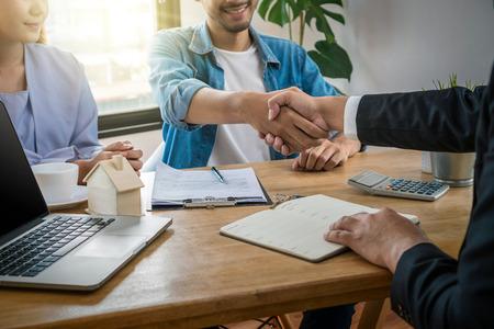 Nahaufnahme Handschlag zwischen Verkaufsvertreter und Hausbesitzer beim Unterschreiben des Kontakts des Hauskaufs oder der Hausmiete auf dem Arbeitsraumtisch im neuen Haus, Umzugs- und Hausjagdkonzept,