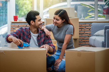 Asian young couple packing the big cardboard box for moving in new house, Moving and House Hunting concept, Stock Photo