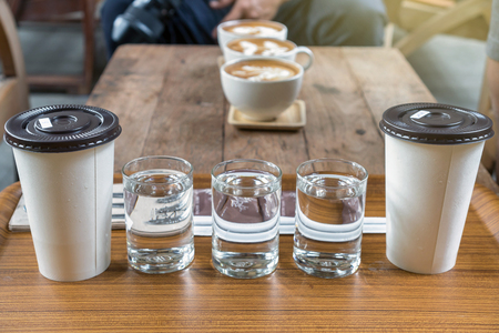Coffee cup set which consist of glassed of water and ice coffee in paper cup over the photo blurred of latte art hot coffee on the wooden table, drink and coffee shop concept